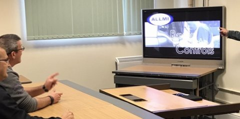 2 students at a desk viewing an ALLMI video