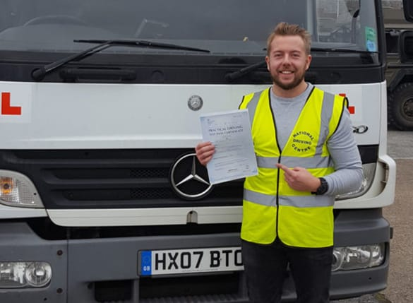 Happy driver 7 standing by vehicle holding pass certificate