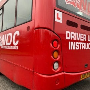 Back of red bus showing learner plate and NDC signage