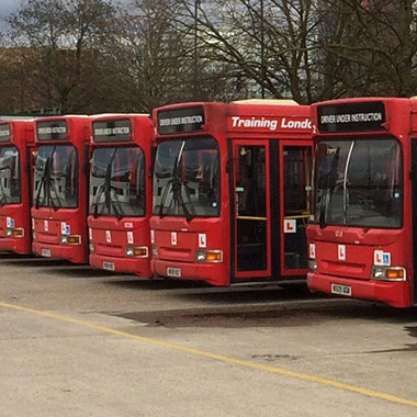 Five red buses parked together