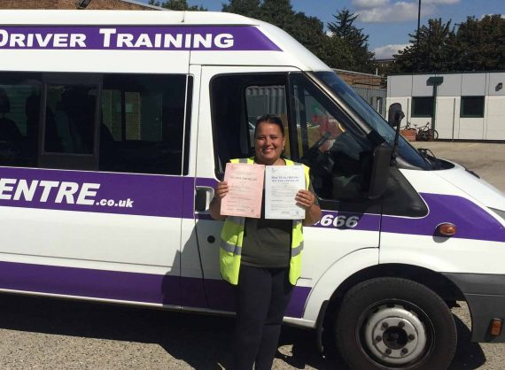 Happy minibus driver 1 standing next to minibus holding pass certificate