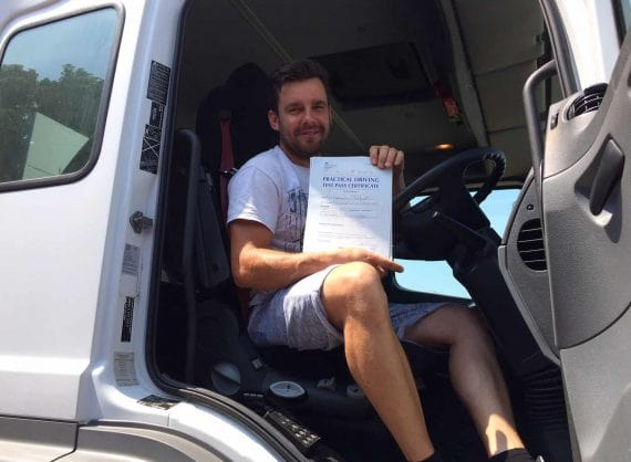 Driver who has just passed his test sitting in driver seat of lorry holding certificate